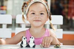 A girl playing with toy pandas at the table Royalty Free Stock Photos