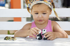 A girl playing with toy pandas at the table Stock Photography