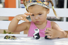 A girl playing with toy pandas at the table Stock Photo