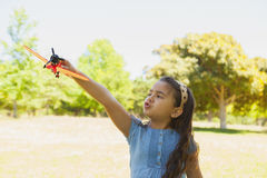 Girl playing with a toy plane at park Royalty Free Stock Images