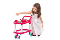 Girl playing with toy pram Royalty Free Stock Photography
