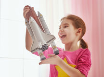 Girl playing with toy rocket. Child girl playing with toy rocket and dreaming of becoming a spacemen. Portrait of funny kid near windows Royalty Free Stock Photos