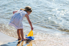 Girl playing with toy  sailboat at the lake Stock Photo