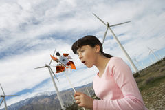 Girl Playing With Toy Windmill At Wind Farm Royalty Free Stock Photos