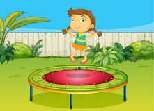 A girl playing on trampoline Stock Images