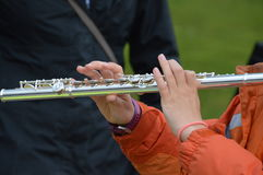 Girl Playing Transverse Flute. Boy playing transverse flute out in a park at Kingsday Amsterdam The Netherlands Royalty Free Stock Image