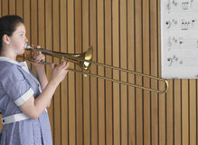 Girl Playing Trombone In Music Class Royalty Free Stock Image