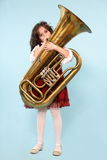 Girl playing Tuba. A girl playing tuba isolated over light blue background Royalty Free Stock Photo