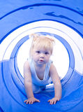 Girl playing in tunnel. Girl playing in blue toy tunnel royalty free stock image