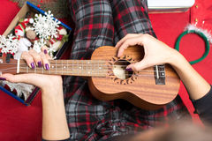 Girl playing ukulele for christmas Stock Photos