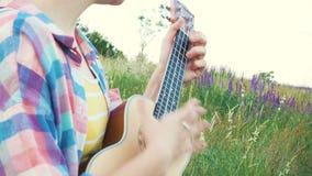 Girl playing on ukulele stock footage
