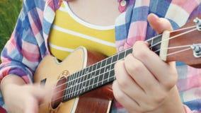 Girl playing on ukulele stock video