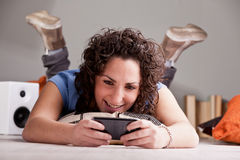 Girl playing videgames on her mobile phone Stock Photography