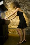 Girl playing video game. A beautiful young woman enthusiastically playing a classic arcade video game, showing the movement of her hair in action Stock Images