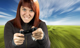 Girl playing video game console. Redhead girl joyfully playing Playstation console Royalty Free Stock Images
