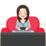 Girl Playing Video Game. Cute teenager girl playing video game sitting on couch indoors Royalty Free Stock Image