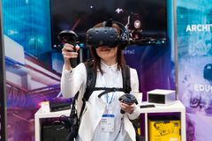 Girl playing video game in virtual reality headset and handheld controllers developed by HTC Vive on exhibition Cebit. Hannover, Germany - March, 2017: Girl Royalty Free Stock Photos