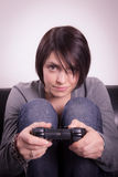 Girl playing video games. On the couch Royalty Free Stock Photos