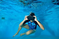 Girl playing video games underwater in the pool in a virtual reality helmet on his head. Virtual reality simulator. Shooting under. Water. Horizontal orientation royalty free stock photos