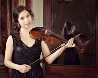 Girl playing  vintage violin near huge vintage mirror Royalty Free Stock Photo