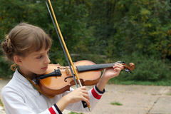 Girl playing the violin Stock Photos