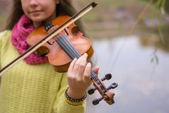 Girl playing the violin in the autumn park at a autumn foliage b. Girl playing the violin in the aun park at a aun foliage background. Violin in the foreground royalty free stock photo