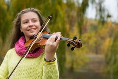 Girl playing the violin in the autumn park at a autumn foliage b. Girl playing the violin and smiling in the autumn park at a autumn foliage background. Violin stock images