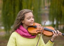 Girl playing the violin eyes closed in the autumn park at a lake. And willow foliage background. Young violinist playing in the park royalty free stock photo