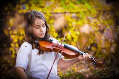 Girl Playing Violin. In a fall day Royalty Free Stock Photography