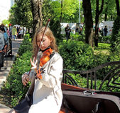 The girl playing the violin for free in the city square Stock Photos