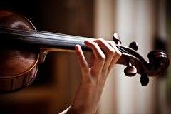 Girl playing violin, holding fingerboard. A picture of a girl playing violin. Hand is holding the fingerboard. Fingers are on the strings. Image includes violin royalty free stock image