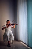 Girl playing violin at home studio low key light Royalty Free Stock Photos