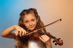Girl playing the violin isolated on gel background Stock Photo