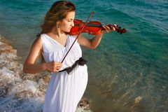 Girl playing violin on sea background Stock Photography
