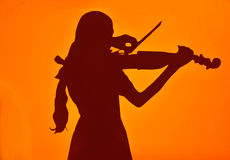 Girl playing the violin. Silhouette of girl playing the violin with orange background stock illustration