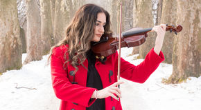 Girl playing violine. Beautiful young girl play with snow stock photos