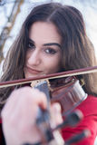 Girl playing violine. Beautiful young girl play with snow royalty free stock image