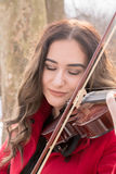 Girl playing violine. Beautiful young girl play with snow stock photography