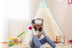 Girl playing with virtual reality headset. Little girl wearing virtual reality headset, playing in a playoom and having fun Stock Photo