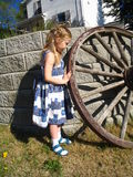 Girl playing with wagon wheel. Cute young girl outside home playing with wagon wheel stock image