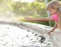 Girl playing with water Stock Images