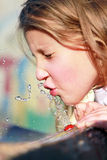 Girl playing with water. Girl playing with drinking water Stock Photography