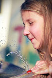 Girl playing with water. In the summer Royalty Free Stock Image