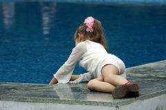 The girl playing with water. In pool Royalty Free Stock Photo