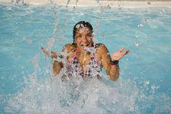 Girl playing in water. A girl playing and splashing water in a pool Royalty Free Stock Photos