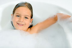 Girl playing with water and foam in a  bathtub Stock Image
