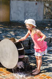 Girl playing with water mill attraction Stock Image