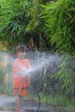 Girl playing water. My daughter holding rubber tube and splash water, outdoor, asian, cute, evening, female, fun, little, play royalty free stock images