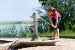 Girl playing at the water pump Stock Photo