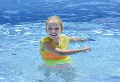 Girl playing in the water of a swimming pool stock photo